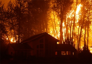A wildfire burns behind a home on Twisp River Road, Thursday, Aug. 20, 2015 in Twisp, Wash. Authorities on Wednesday afternoon urged people in the north-central Washington town to evacuate because of a fast-moving wildfire. (AP Photo/Ted S. Warren)